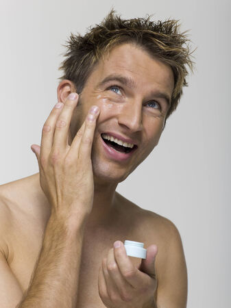 Young man applying face cream