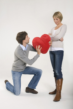 Young man giving woman heart-shaped cushion kneeling photo