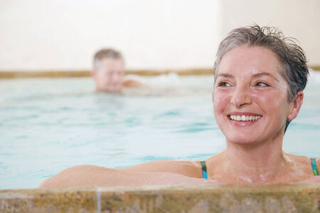 Mature couple in swimming pool woman smiling by pools edge man further behind photo