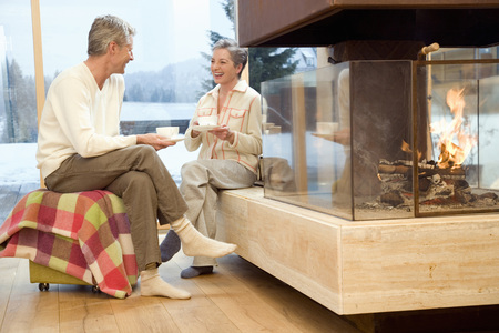 Mature couple sitting in front of fireplace holding tea cup Stock Photo