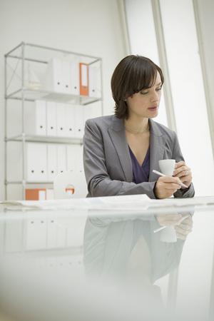 tomando refresco: Empresaria que sostiene una taza de caf� toma de notas
