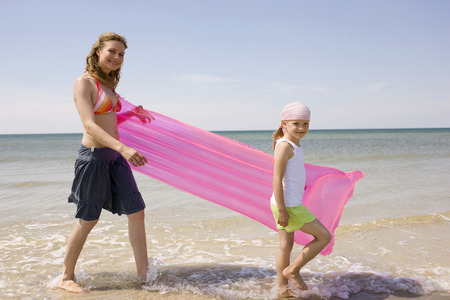 bed skirt: Mother and daughter walking on beach carrying airbed