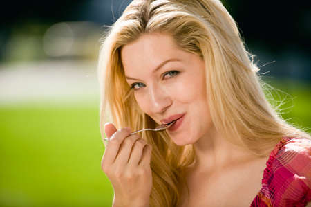 Germany, Bavaria, Upper Bavaria, Young woman licking spoon Stock Photo