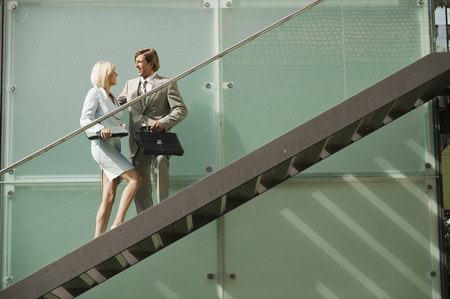 Business people standing on stairs having conversation photo