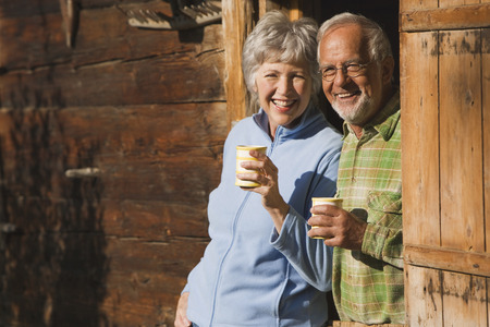 Austria, Karwendel, Senior couple leaning on log cabin's entrance holding mugs Stock Photo - 29823875