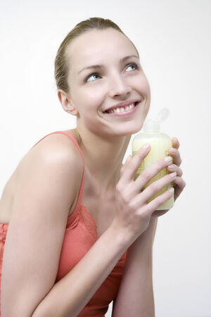 Young woman holding bottle with bath lotion, portrait photo