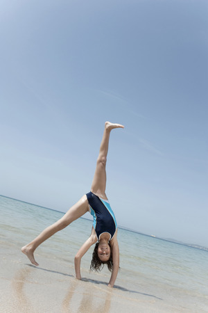 Spain Mallorca Girl doing handstand on beach Stock Photo