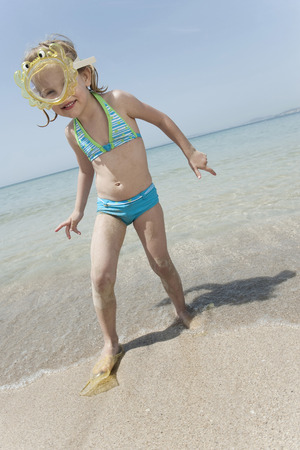Spain, Mallorca, cute little girl on the beach wearing diving goggles photo
