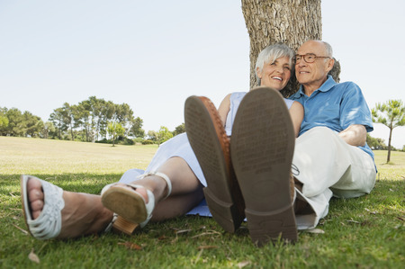 summer shoes: Spain Mallorca senior couple sitting by tree relaxing Stock Photo