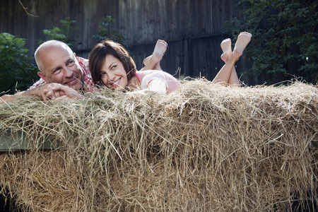 bald man: Germany, Bavaria, Couple lying on haystack Stock Photo
