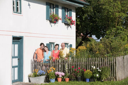 Germany, Bavaria, Four people standing by the fence in garden