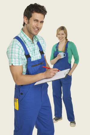 workwoman: Man in overall writing on clipboard, woman standing in background Stock Photo