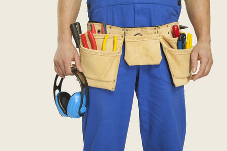 ear muff: Man wearing tool belt and holding ear muff mid section close-up
