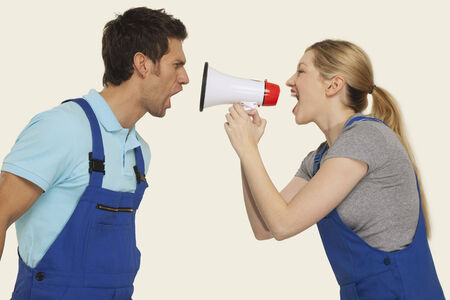 overall: Worker in overall yelling female boss in overall shouting through megaphone with each other