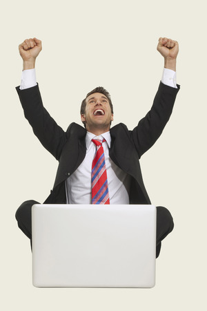 clenching: Businessman with laptop, clenching fist.