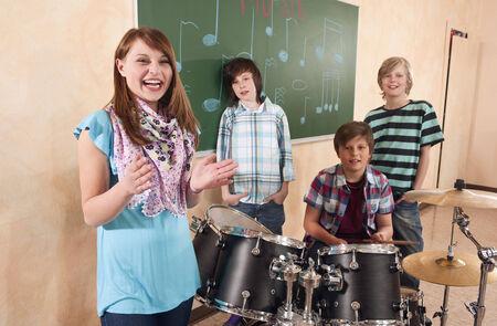 bateria musical: Los estudiantes de la niña de la clase de música que aplaude sonriente muchacho tocando la batería de pie detrás de sus compañeros de clase