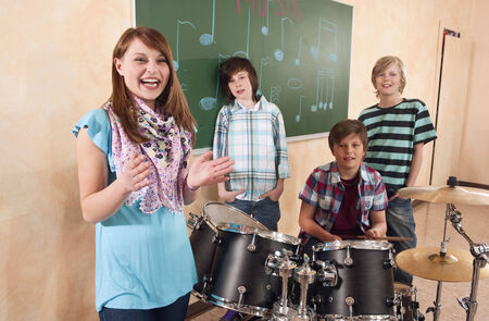Students at music class girl clapping smiling  boy playing drums classmates standing behind