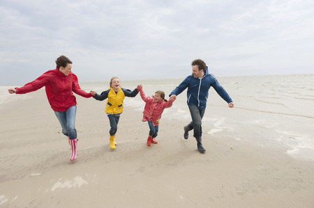 girls holding hands: Germany, St. Peter-Ording, North Sea family holding hands and running on beach Stock Photo