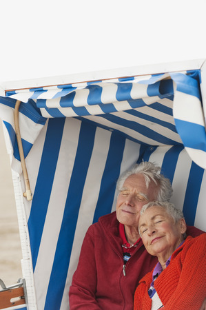 Germany, North Sea, St.Peter-Ording, Senior couple resting on hooded beach chair photo