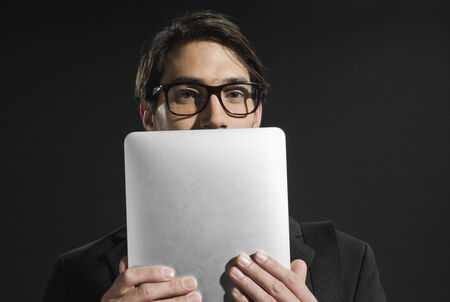obscured: Young businessman holding tablet face partly obscured Stock Photo