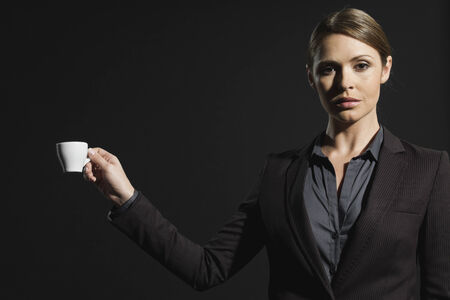 supercilious: Young businesswoman holding coffee cup