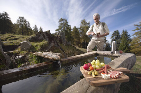 Mature man standing at trough having snacks photo
