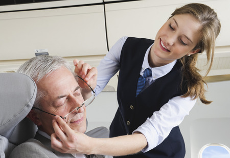 Senior passenger sleeping on airplane while air hostess is removing glasses photo