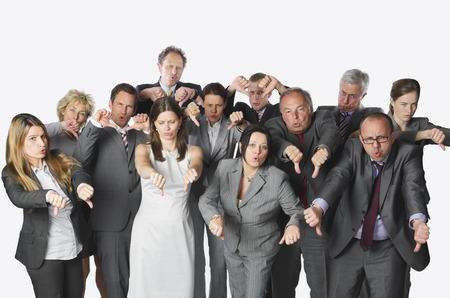 THUMBS DOWN: Large group of business people showing thumbs down against white background Stock Photo