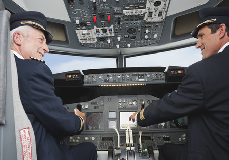 Senior captain and co-pilot driving airplane in cockpit Stock Photo