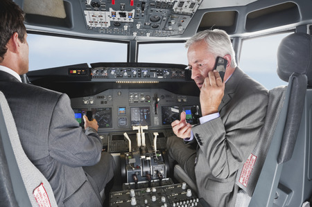 negligent: Two businessmen driving airplane in cockpit and using mobile phone at the same time