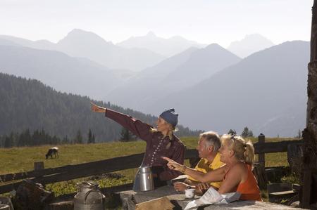 Couple at mountain hut, talking to peasant woman photo