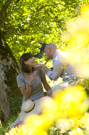 Couple having picnic under tree Stock Photo