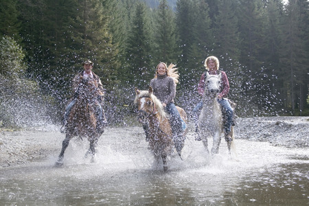 spattering: Austria, Salzburger Land, Altenmarkt, Young people riding horses across river Stock Photo