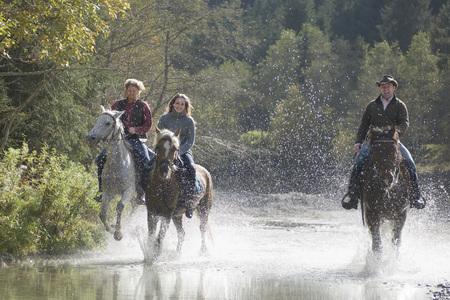 Austria, Salzburger Land, Altenmarkt, Young people riding horses across river Reklamní fotografie