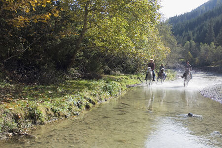Austria, Salzburger Land, Altenmarkt, Young people riding horses across river photo