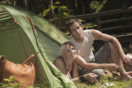 Austria, Steiermark, Young couple camping, woman lying in tent photo