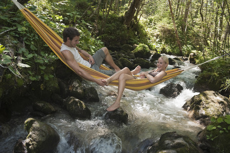 Austria, Steiermark, Young couple lying in hammock above stream photo