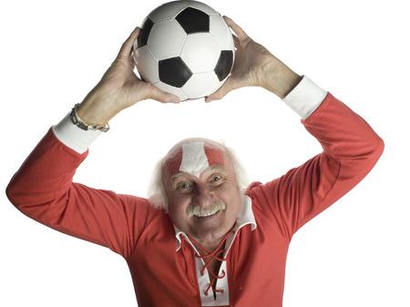 Senior man holding football above head, portrait Stock Photo