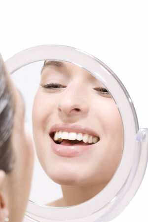 self conceit: Young woman looking into mirror, smiling, portrait