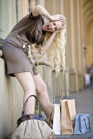 freaking: Germany, Bavaria, Munich, Young woman with shopping bags, leaning against house walls, freaking out
