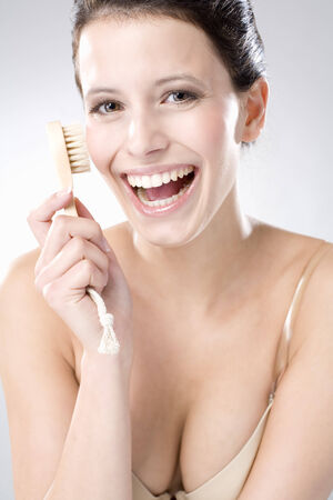Young woman using peeling brush, laughing, close up