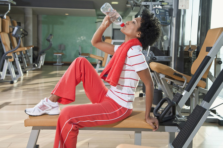 water activity: Germany, Bavaria, Woman drinking water in gym, side view, portrait