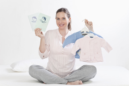 future twin: Pregnant woman holding baby clothes, smiling, portrait