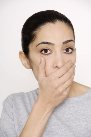 obscuring: Young woman covering mouth with hand, portrait