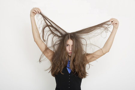 puzzlement: Young woman lifting her hair