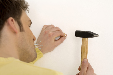 Man hammering nail into wall, close-up photo