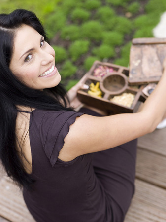 elevated view: Woman holding incense box, smiling, elevated view Stock Photo