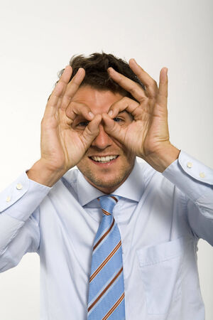 probing: Young businessman making circles around eyes with fingers, portrait