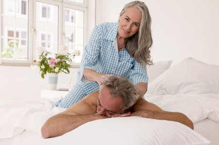 mature men: Mature woman giving massage to mature men in bed