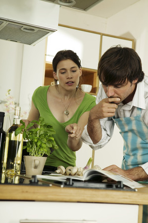 pointing herbs: Young couple looking at recipe book in kitchen, low angle view Stock Photo